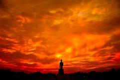 Buddhastaty i konturplats på solnedgången Arkivfoto