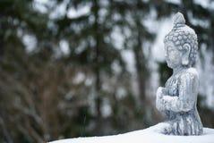 Buddhastaty med snöfall och insnöad vinter royaltyfri fotografi