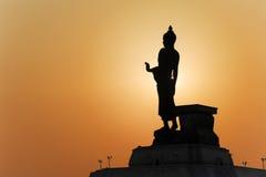 Buddhastaty och solnedgången Arkivfoto
