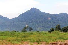 Buddhastaty på berget med molnigt Arkivbild
