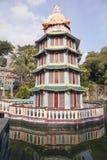 Buddhastaty som överst sitter av pagod Arkivfoto