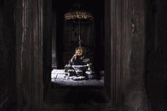 Buddhastaty som slås in i guld-, fortfarande lugna från morgonljuspasserandet till och med fönstret av den Bayon templet på Angko fotografering för bildbyråer
