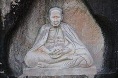 Buddhastaty som snidas på grottaväggen arkivbilder