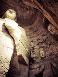 Buddhastatyer Kina som snidas i grotta Arkivbild