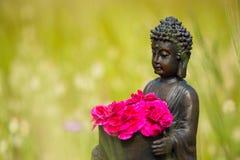 Buddhastatyett med röda blommor Arkivbild