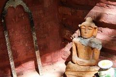 Buddhastatyn lutar på den gamla röda väggen Royaltyfri Bild