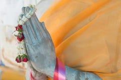 Buddhastatyn satte gömma i handflatan av händerna tillsammans i honnör Arkivbilder