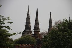 Ancient Round And Bell Shape Pagodas With Green Leaves. Ruins and old Buddhist historical park with clear gray sky and bricks walls in Ayutthaya Thailand stock photos