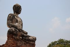 Ancient Temple With One Buddha Statue. Ruins.  Old Buddha statuary with bricks seat base Buddhist historical park. summertime in Ayutthaya Thailand royalty free stock image