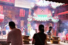 Buddhish devotees praying at a Chinese temple in Kuala Lumpur stock photo