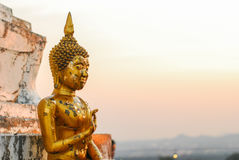 Buddhish statue. The evening sun shines on the gilded Buddha at the top of the mountain Royalty Free Stock Photo