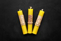Buddhism. Candles with Yantras and mantras in sanskrit on black background top view copy space. Buddhism. Candles with Yantras and mantras in sanskrit on black royalty free stock images