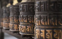 Buddhism obsolete prayer wheels in row Stock Photography