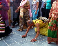 Buddhism Religious Holiday Kathmandu Nepal. A man making prostrations in devotion among a crowd of people from various ethnic groups in the Boudha neighborhood Stock Image