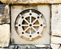 Buddhism's wheel symbol. Ceramic tile in old rock wall with buddhist wheel, a religious symbol representing buddhism's noble eightfold path. Tile is one of a royalty free stock images