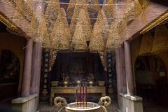 Incense sticks burning in Buddhist temple. In Buddhism, it is a sacred offering, a way to honor the Triple Gem of the Buddha, his Dharma and the Sangha. The Stock Image