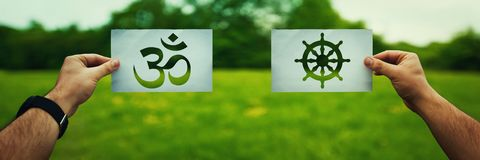Buddhism vs Hinduism. Religion conflicts as global issue concept. Two hands holding different faith symbols, Buddhism vs Hinduism belief over green field nature royalty free stock photo
