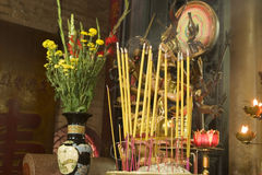 Buddhist Altar and Incense. An altar in a Buddhist temple in Vietnam. In the foreground, an urn is filled with burning incense sticks giving off smoke. A flower royalty free stock photos