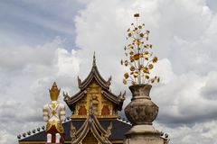 Buddhist background with amazing cloudy sky, buddhist statue, traditional temple and golden flower royalty free stock photos