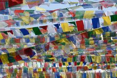 Buddhist bright prayerful flags with religious text in Sanskrit against blue sky background. Royalty Free Stock Photography
