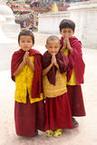 Buddhist monk boys pray. Buddhist children give blessing, with hands together, wearing red and white religious garments, next to Boudhanath Stupa. Kathmandu Stock Photography
