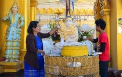 Buddhist devotees bathing Buddha statues at Shwedagon Pagoda. Yangon, Myanmar - Jan 15, 2015. Buddhist devotees bathing Buddha statue for blessings at Shwedagon royalty free stock images
