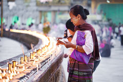 Buddhist devotees lighting candles Royalty Free Stock Images