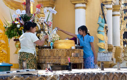 Buddhist devotees pouring water on Buddha image Royalty Free Stock Image