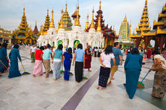 Buddhist devotees sweeping the compound Royalty Free Stock Image