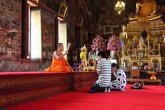 Buddhist devotees at Wat Arun temple. A Budhhist monk and devotees do prayers at Wat Arun temple at Bangkok stock image