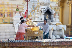 Buddhist family devotees pours water to statue of Royalty Free Stock Photo