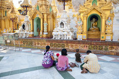 Buddhist family devotees prays to statue of Buddha Stock Photos