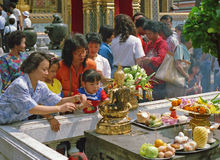 Buddhist family praying. Bangkok, Thailand- February 20, 1989: A Buddhist family give offerings of food and place gold foil on a statue of Buddha at the Grand Stock Photography