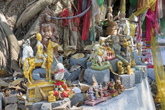 Buddhist figures among the roots of an old tree Royalty Free Stock Images