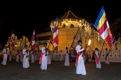 Buddhist flag bearers begin their march past the Temple of the Sacred Tooth Relic in Kandy in Sri Lanka during the Esala Perahera. Stock Images