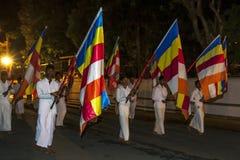 Buddhist Flag Bearers parade through the streets of Kandy during the Esala Perahera in Sri Lanka. Royalty Free Stock Photos