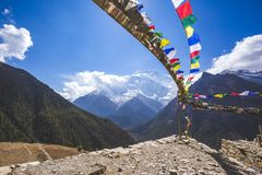 Buddhist flags. Annapurna circuit trek. Himalayan mountains, Nepal. Multicolored Buddhist flags. Himalayan mountains of Nepal. Annapurna circuit trek royalty free stock photo
