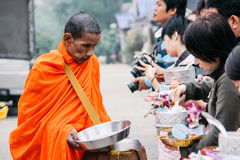 Buddhist giving alms with foods and flowers to a Buddhist Monk at Sangkhlaburi`s Mon Village royalty free stock photography