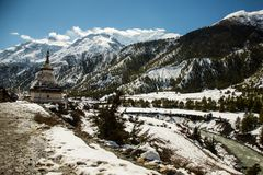 A Buddhist Gompa or Stupa on the Annapurna circuit route near Manang village on snow peaks background. Trekking in Nepal. Scenic view of Himalayas royalty free stock photography