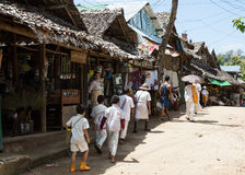 Buddhist Karen in refugee camp. TAK THAILAND - SEP27 : A row of Buddhist Karen in white dress walking along the alley for donation in the refugee camp Ban Maehla Stock Photography