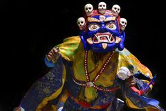 A Buddhist lama in a ritual Tibetan costume and a mask of Blue Mahakala perform the sacred Cham Dance. Stock Images