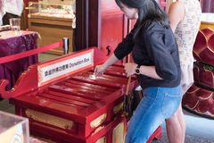 Buddhist make a merit into donation box at Buddha Tooth Relic Temple and Museum. Buddha Tooth Relic Temple and Museum, Singapore - September 5,2017 - Buddhist Royalty Free Stock Image