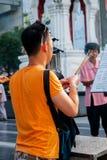 Buddhist man prays, near big shopping mall, Bkk Stock Images