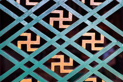 Buddhist manji symbol seen in a detail of a wooden window frame at a Hong Kong temple Stock Photography