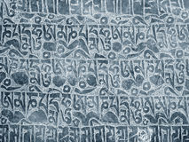 Buddhist mantra carved in stone. As background Stock Photos