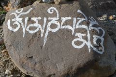 Buddhist Mantra Om Mani Padme Hum painted on the stone stock images