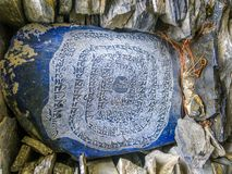 Buddhist mantras in engraved in a colorful stone - Annapurna circuit - Nepal. Buddhist mantras in engraved in a colorful stone - Annapurna circuit in Nepal royalty free stock images