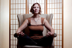 Buddhist meditation. A beautiful young woman meditates whilst sitting cross-legged in an armcahir Stock Images