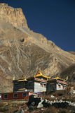 Buddhist monastery in highlands of Nepal near Tibet. Big rock on background. View from Muktinath village Stock Photos