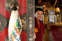Buddhist monastery monk. Buddhist monk opening the doors of a monastery.  Kathmandu, Nepal Stock Photos